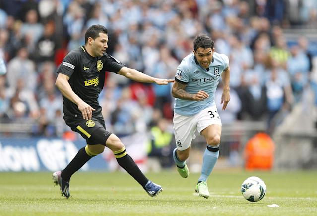 Wigan Athletic's Antolin Alcaraz (left) and Manchester City's Carlos Tevez (right) battle for the ball