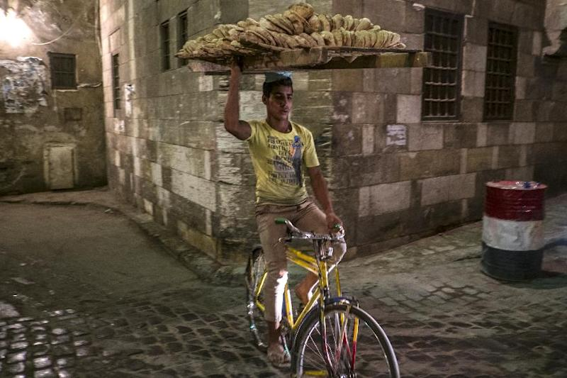 A bread seller rides his bicycle as Muslim worshipers break the day-long fast during the holy month of Ramadan in Cairo's Khan el-Khalili district on July 8, 2014 (AFP Photo/Khaled Desouki)