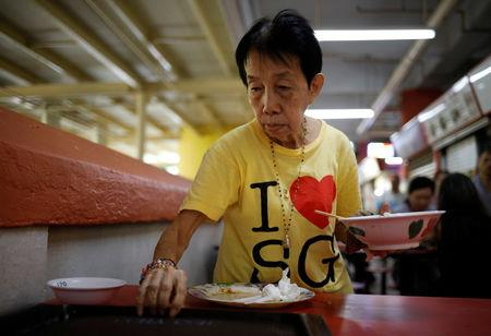 Cleaner Mary Lim, 71, clears tables at a food centre in Singapore December 13, 2018. REUTERS/Edgar Su/Files