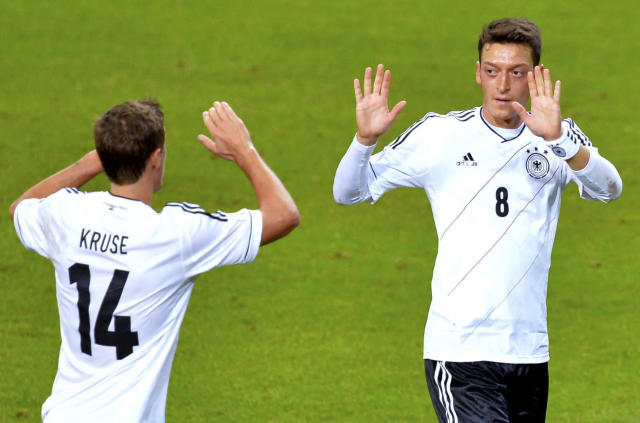 FILE - This is a Tuesday, Oct. 15, 2013 file photo of Germany's Mesut Ozil, right, as he celebrates scoring his team's first goal with team mate Max Kruse during the 2014 World Cup group C qualifying soccer match between Sweden and Germany at Friends Arena in Stockholm, Sweden. (AP Photo/TT/Jonas Ekstromer,File)