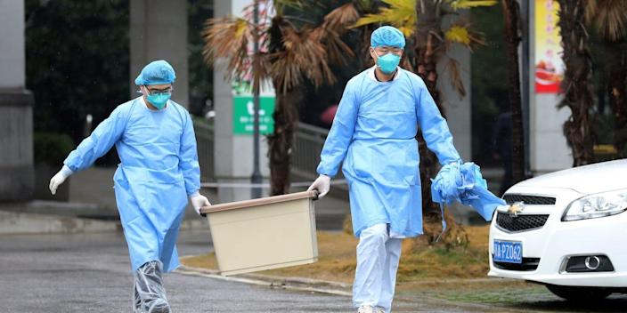 Medical staff carry a box by the Jinyintan hospital in Wuhan, which houses patients with the coronavirus, on January 10, 2020.