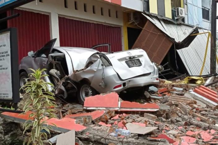 A damaged car and buildings are seen following an earthquake in Mamuju