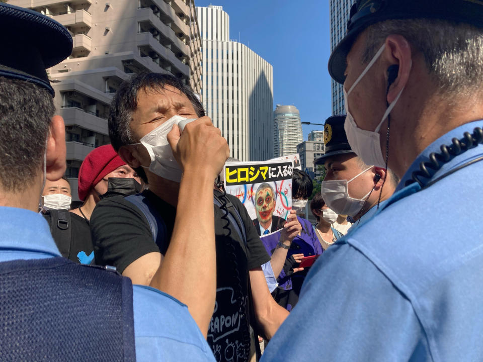 """Protesters against the Olympic and Paralympic Games (Tokyo 2020) confront police officers in Tokyo, Saturday, July 10, 2021. The poster, center, reads, """"Don't enter Hiroshima,"""" with a picture of International Olympic Committee President Thomas Bach and graffiti over his face, as local media report Bach is scheduled to visit Hiroshima later this month ahead of the 2020 Summer Olympics starts. (AP Photo/Kwiyeon Ha)"""