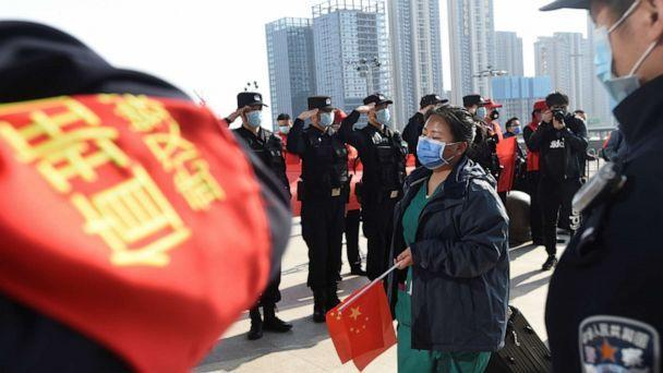 PHOTO: Chinese police officers salute as a medical worker arrives at the Wuhan Railway Station before leaving the epicenter of the novel coronavirus outbreak, in the city of Wuhan in China's central Hubei province, March 17, 2020. (Reuters)