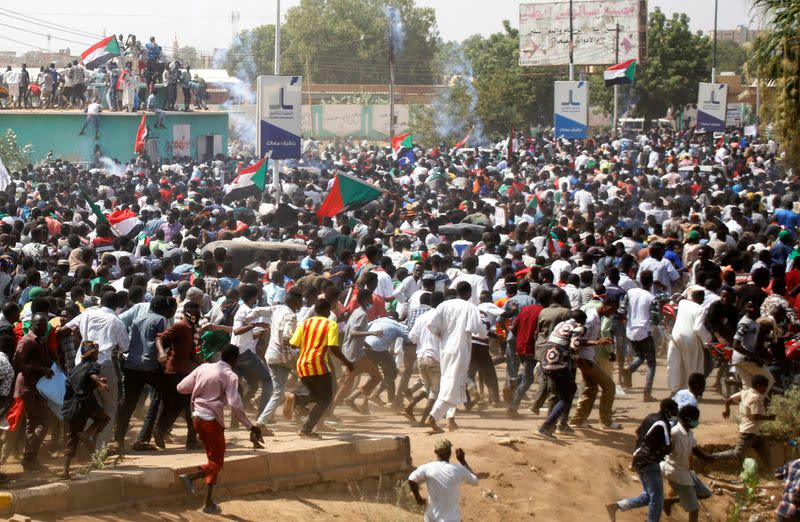 Protesters run after they were dispersed by riot-police officers near the Parliament buildings, in in Omdurman, Khartoum