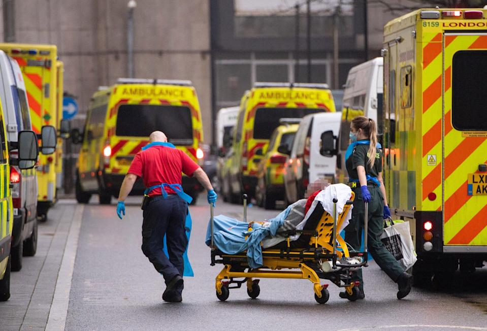 Paramedics unloading a patient from an ambulance outside the Royal London Hospital (PA Wire)