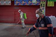 "Cleaning personnel spray disinfectant at the ""Central de Abasto,"" Mexico City's giant food wholesale market"