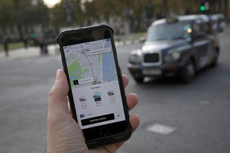 FILE PHOTO: A photo illustration shows the Uber app on a mobile telephone, as it is held up for a posed photograph, with a London Taxi in the background, in London