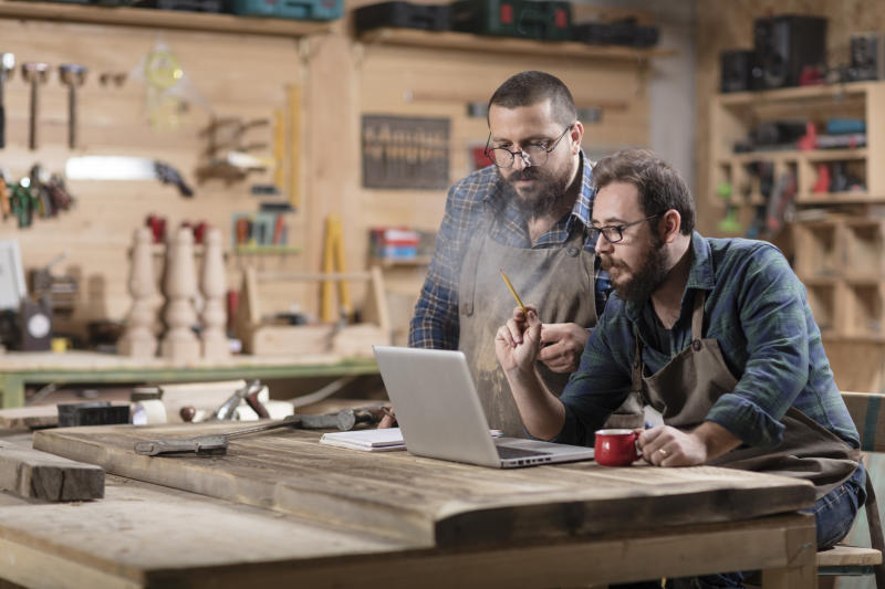 Two workmen looking at laptop in the middle of a workshop.