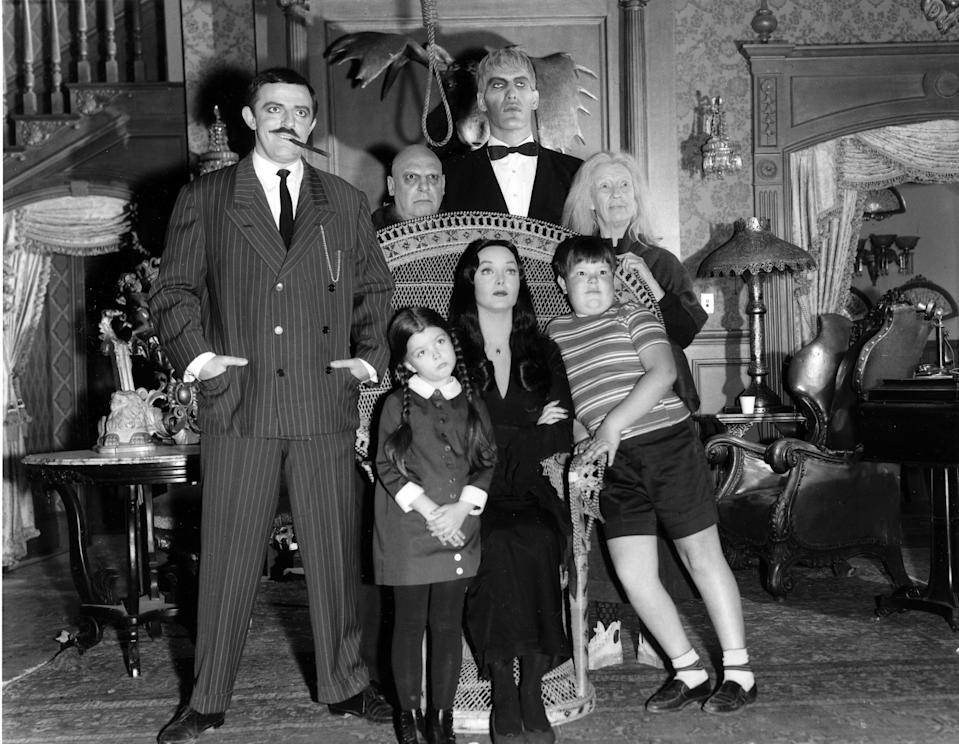 "UNITED STATES - SEPTEMBER 18:  THE ADDAMS FAMILY - Pilot - Season One - 9/18/64, ""The Addams Family"" was based on the characters in Charles Addams' ""New Yorker"" cartoons. The wealthy Gomez Addams (John Astin, left) was madly in love with his wife, Morticia (Carolyn Jones, seated), and their two children, Wednesday (Lisa Loring) and Pugsley (Ken Weatherwax). The family, including Uncle Fester (Jackie Coogan), their towering butler Lurch (Ted Cassidy), Grandmama (Blossom Rock), and Thing, a hand that usually appeared out of a small wooden box, resided in an ornate, gloomy mansion.,  (Photo by Walt Disney Television via Getty Images Photo Archives/Walt Disney Television via Getty Images)"