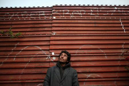 Joaquin, 36, a chef from Guatemala who says he was deported from the United States, poses for a photograph while leaning on a section of the border fence separating Mexico and the United States, in Tijuana, Mexico, February 26, 2017.   REUTERS/Edgard Garrido
