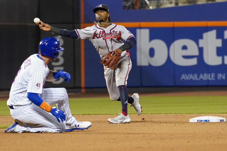 Atlanta Braves' Ozzie Albies completes a double play after forcing New York Mets Jeff McNeil out off a hit by J.D. Davis during the eighth inning of a baseball game, Wednesday, July 28, 2021, in New York. (AP Photo/Mary Altaffer)
