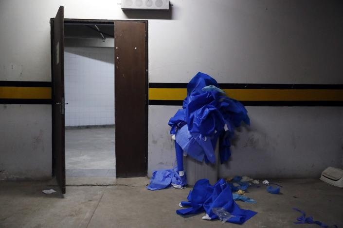 Used security gear worn in the COVID-19 area overflows a trash can at Clinicas Hospital in San Lorenzo, Paraguay, Tuesday, April 20, 2021. (AP Photo/Jorge Saenz)