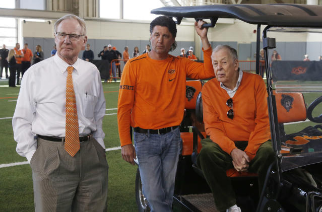 Oklahoma State University President Burns Hargis, left, head football coach Mike Gundy, center, and T. Boone Pickens, right, watch during an NCAA college football Pro Day in Stillwater, Okla., Thursday, March 15, 2018. (AP Photo/Sue Ogrocki)