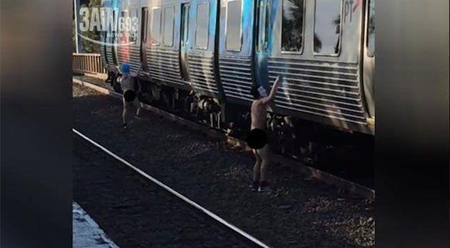 A duo of naked men have been caught on video appearing to spray-paint graffiti on a Melbourne train in broad daylight. Picture: 3AW