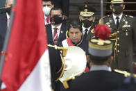 Peru's newly sworn-in President Pedro Castillo removes his hat momentarily to acknowledge the Peruvian flag held by soldiers outside Congress on his inauguration day in Lima, Peru, Wednesday, July 28, 2021. (AP Photo/Francisco Rodriguez)