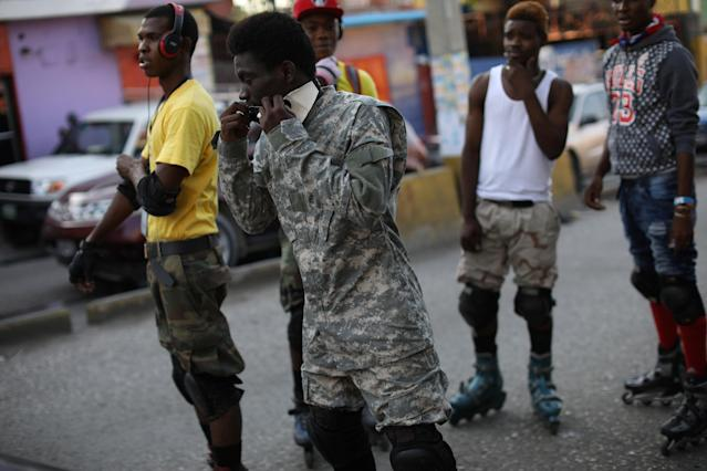 A youth covers his face before skating down a street in Port-au-Prince, Haiti, March 18, 2018. REUTERS/Andres Martinez Casares