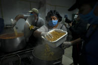 Cooks prepare pasta at a soup kitchen at the San Cayetano church in Jose Leon Suarez neighborhood on the outskirts of Buenos Aires, Argentina, Tuesday, March 31, 2020. The Argentine government said Tuesday that the number of people requesting food assistance has increased following the lockdowns that have left many people unable to work amid the COVID-19 pandemic. (AP Photo/Victor R. Caivano)