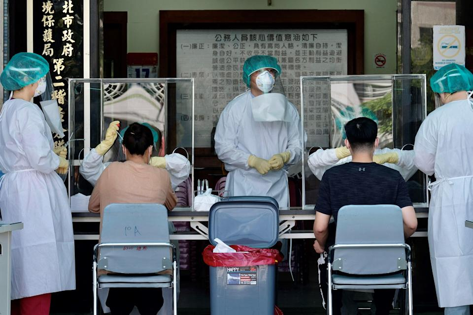 <p>Medical staffers collect samples from local residents during a COVID-19 corona virus testing at the Xindian District in New Taipei City </p> (AFP via Getty Images)