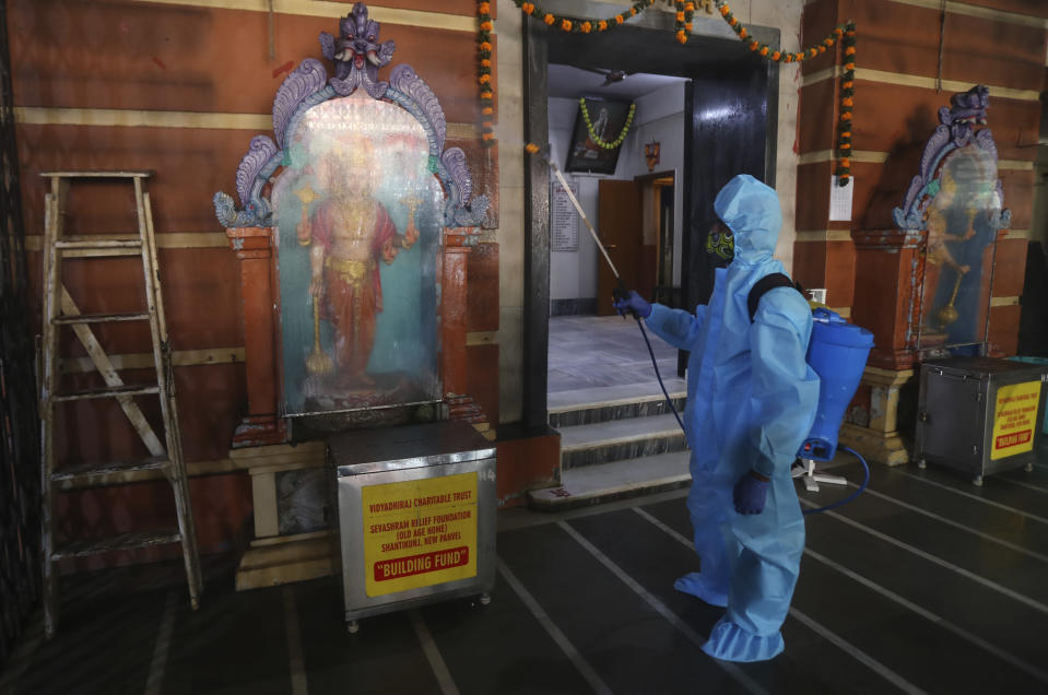 An employee sanitizes a Hindu temple in Mumbai, India, Sunday, Nov. 15, 2020. India is second in the world in total reported coronavirus cases behind the U.S., but daily infections have been on the decline since the middle of September. (AP Photo/Rafiq Maqbool)