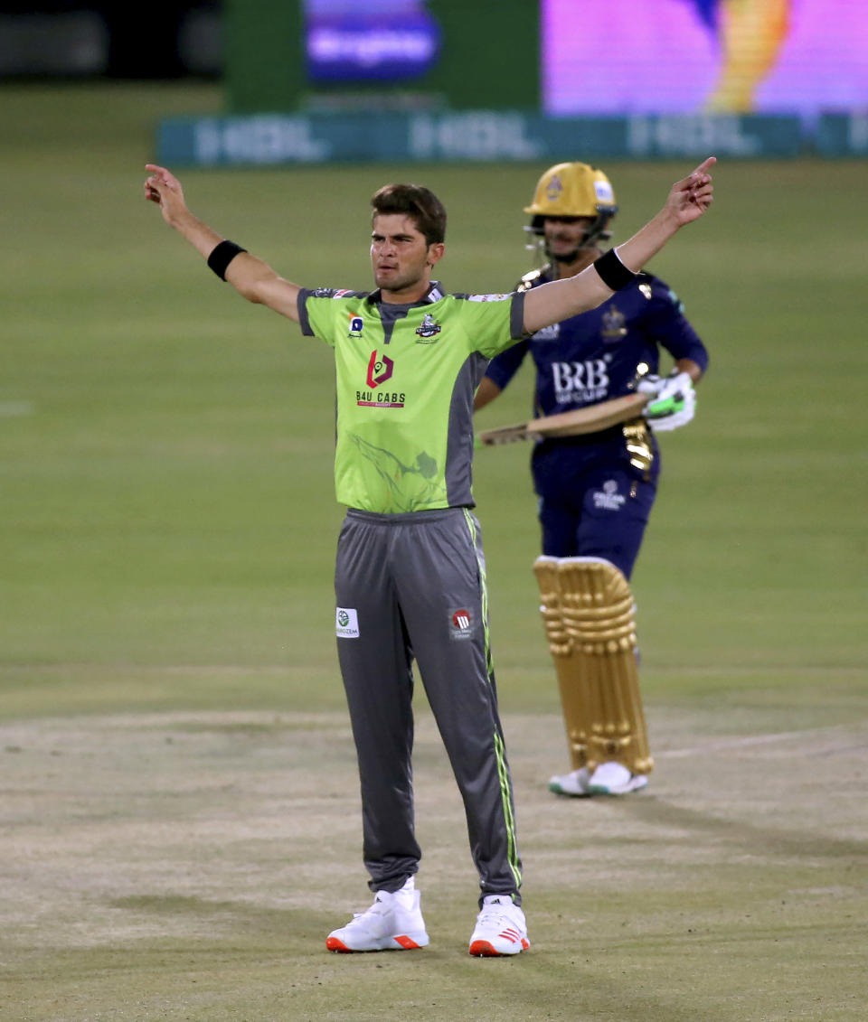 Lahore Qalandars' Shaheen Afridi, front, celebrates after taking the wicket of Quetta Gladiators' Saim Ayub, back, during a Pakistan Super League T20 cricket match between Lahore Qalandars and Quetta Gladiators at the National Stadium, in Karachi, Pakistan, Monday, Feb. 22, 2021. (AP Photo/Fareed Khan)