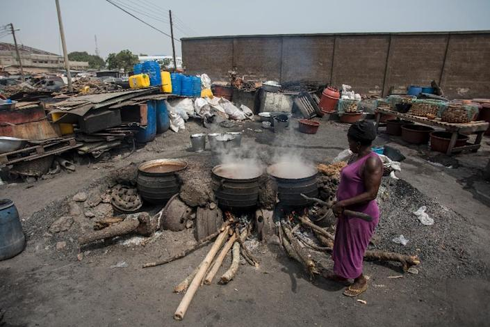 Cauldrons pf the traditional sorghum-based pito drink bubble away in fire pits in Tema, Accra (AFP Photo/CRISTINA ALDEHUELA)