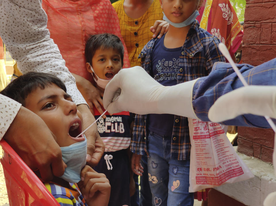 "A health worker takes swab sample of children to test for COVID-19 in Prayagraj, India, Thursday, April 8, 2021. Nations around the world set new records Thursday for COVID-19 deaths and new coronavirus infections, and the disease surged even in some countries that have kept the virus in check. Indian Prime Minister Narendra Modi urged people to get vaccinated, writing in a tweet: ""Vaccination is among the few ways we have to defeat the virus. If you are eligible for the vaccine, get your shot soon."" (AP Photo/Rajesh Kumar Singh)"