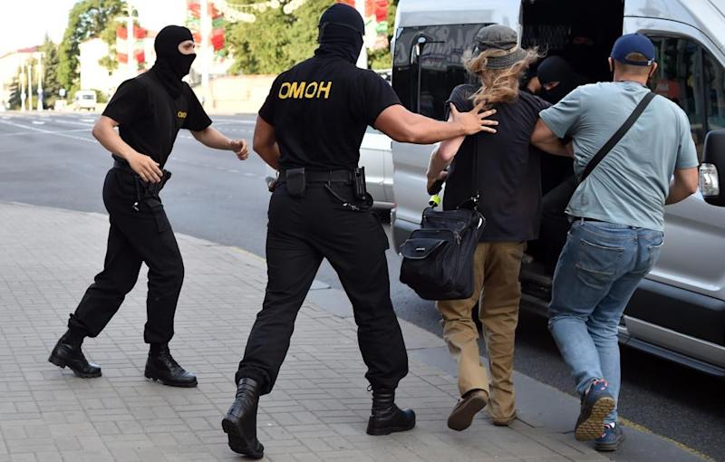 Belarus riot police detain a man on Saturday during an opposition rally on the eve of the presidential election in central Minsk.