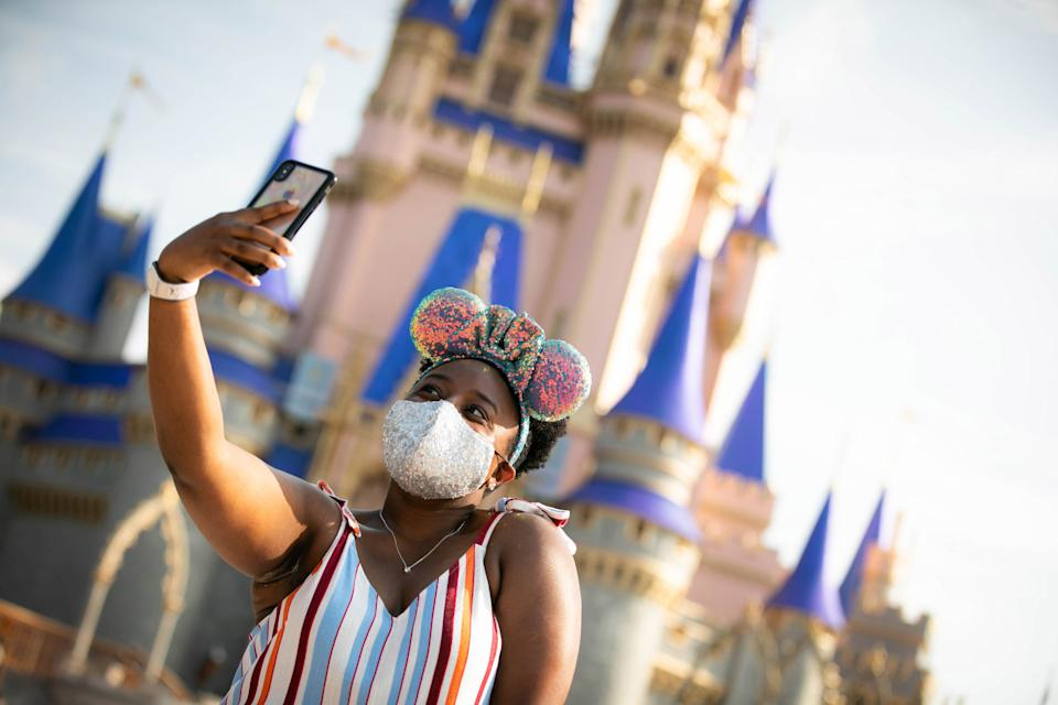 A guest wearing sequin Mickey Mouse ears stops to take a selfie at Magic Kingdom Park at Walt Disney World Resort on July 11, 2020 in Lake Buena Vista, Florida