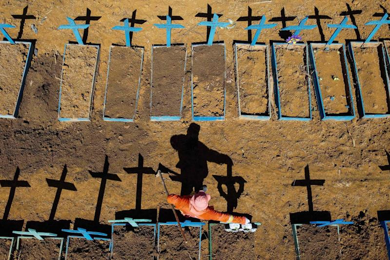 This file aerial photo taken on June 2, 2020 shows a gravedigger standing at the Nossa Senhora Aparecida cemetery where COVID-19 victims are buried daily, in the neighbourhood of Taruma, in Manaus, Brazil: AFP via Getty Images