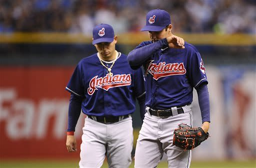 Cleveland Indians shortstop Asdrubal Cabrera, left, walks out to speak to starting pitcher Trevor Bauer as Bauer reacts after walking the bases loaded on the first three Tampa Bay Rays batters during the first inning of a baseball game on Saturday, April 6, 2013, in St. Petersburg, Fla. (AP Photo/Brian Blanco)