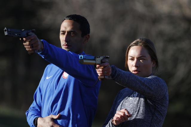 USA Olympic modern pentathlon team members Amro ElGeziry and his wife, Isabella Isaksen practice shooting at targets in a park in Colorado Springs, Colo., Friday, April 24, 2020. Amro Elgeziry and Isabella Isaksen are just your ordinary married Olympic modern pentathlon couple trying to navigate their way through the challenges of training during the coronavirus pandemic. Their sport consists of five events, but they can't practice equestrian horse jumping or swimming at the moment with the facilities closed. For the rest, they improvise. They practice their fencing footwork in the backyard, shoot laser pistols at a target in a nearby park and squeeze in early morning runs along trails as they train for the Tokyo Games in 2021. (AP Photo/David Zalubowski)