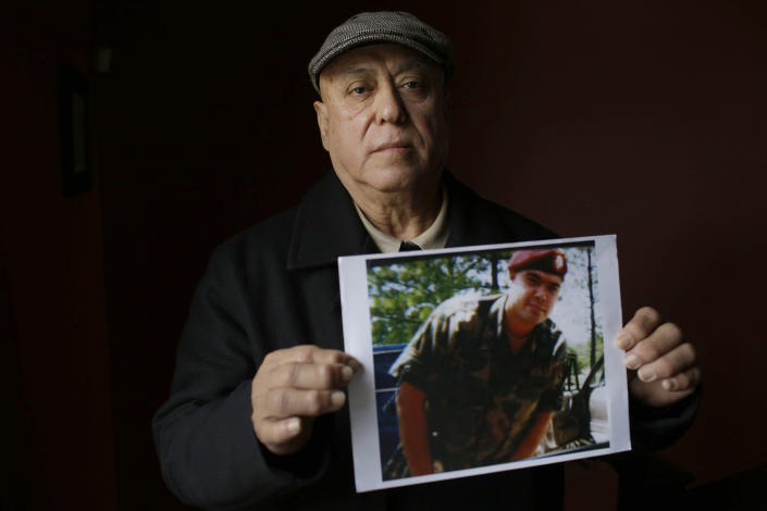 Miguel Perez with a photo of his son Miguel Perez-Montes. Perez-Montes, an Army veteran who did two tours in Afghanistan, was deported after spending seven years in prison on a drug conviction. (Photo: Joshua Lott/AFP/Getty Images)