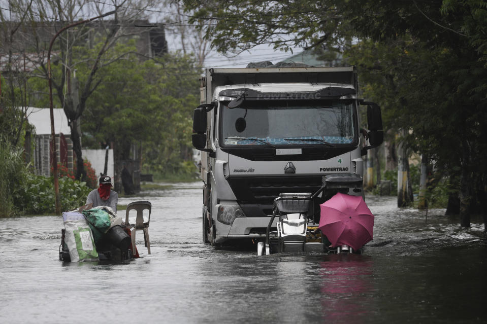 Motorists with an umbrella negotiate a flooded road due to Tyophoon Molave in Pampanga province, northern Philippines, Monday, Oct. 26, 2020. A fast-moving typhoon forced thousands of villagers to flee to safety in provinces south of the Philippine capital Monday, flooding rural villages and ripping off roofs, officials said. (AP Photo/Aaron Favila)
