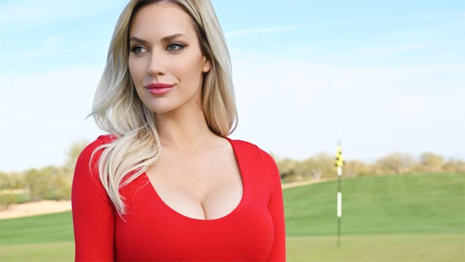 Paige Spiranac is seen here standing on the green of a golf course.