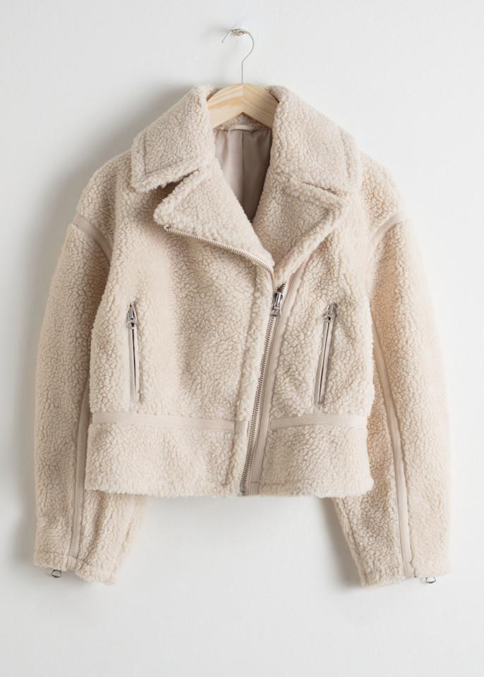 """Teddy coats are one of the few coat trends that everyone can truly agree on. Another coat that everyone loves? The moto jacket! It's a classic. This & Other Stories shearling jacket basically combines the two silhouettes into a fluffy cropped coat that's also incredibly cool. $179, & Other Stories. <a href=""""https://www.stories.com/en_usd/clothing/jackets-and-coats/product.cropped-faux-shearling-jacket-cream.0685997001.html"""">Get it now!</a>"""