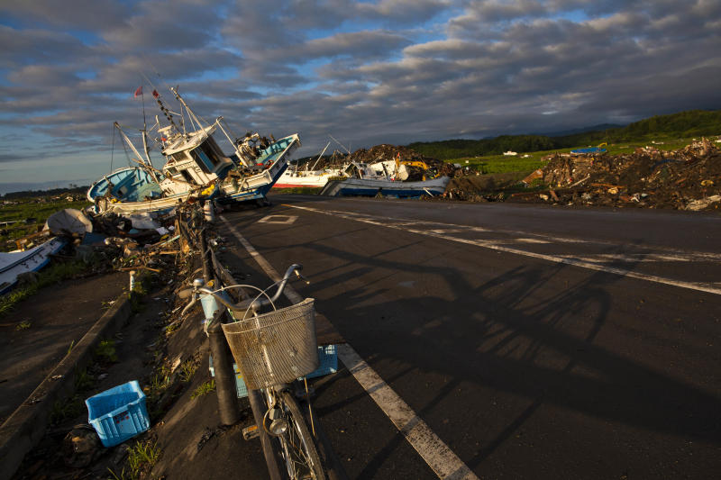 In this July 24, 2011 photo, an abandoned bicycle rests on a road partially blocked by ships that washed ashore in the town of Namie, inside the 20-kilometer (12-mile) exclusion zone around the Fukushima Dai-ichi nuclear plant, in northeastern Japan. A year after a tsunami crippled the plant and caused widespread radiation leaks, a massive and complex cleanup has begun, but experts say areas inside the nuclear exclusion zone will be difficult to decontaminate. (AP Photo/David Guttenfelder)