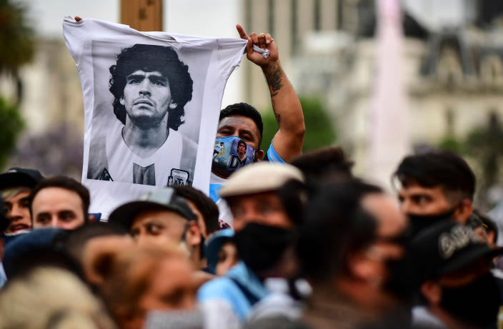 Image: A man waves a t shirt with a picture of Diego Maradona as fans wait to enter the Government House to pay tribute to the late football legend in Buenos Aires (Ronaldo Schemidt / AFP - Getty Images)