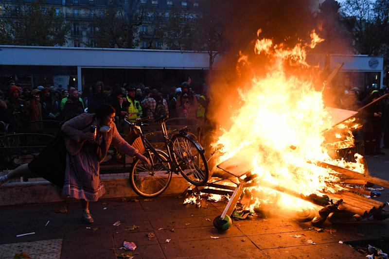 A woman throws a bike into a burning blockade in Paris (AFP via Getty Images)