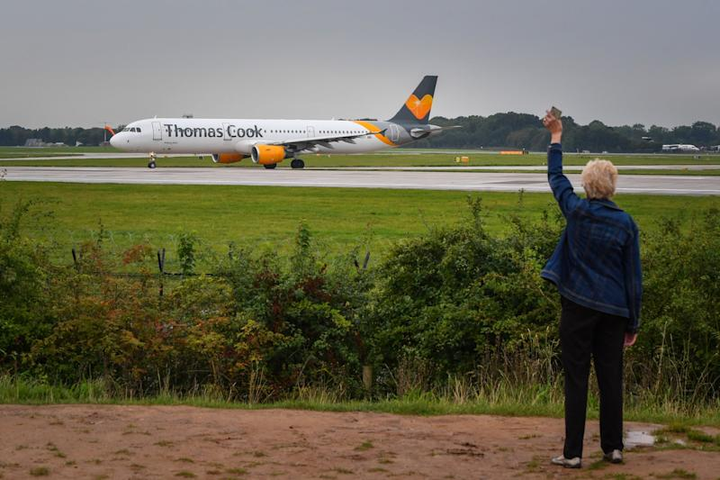 A woman waves as a Thomas Cook aircraft departs from Terminal 1 at Manchester Airport: Getty Images