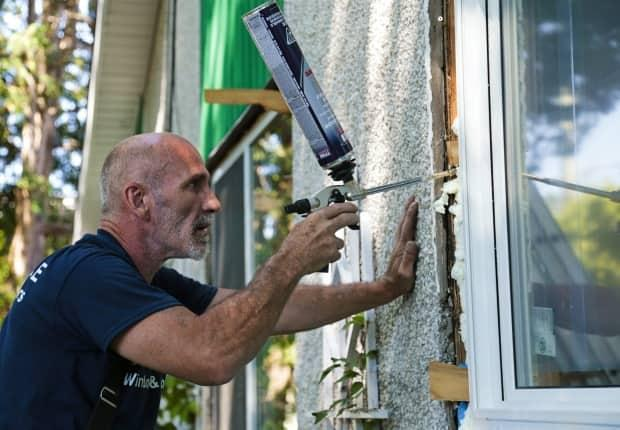Window installer Michel Lauzon insulates a window at a job site in Ottawa. New windows would be part of the local retrofit program. (Marc-André Cossette/CBC - image credit)
