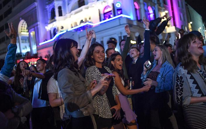 People are seen dancing to a busker in Leicester Square on Saturday night   - Peter Summers/Getty Images