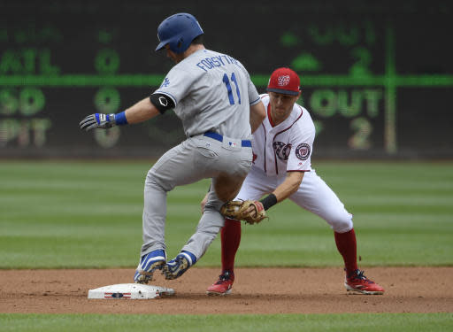 Los Angeles Dodgers' Logan Forsythe, left, is safe at second with a double against Washington Nationals shortstop Trea Turner, right, during the second inning of a baseball game, Sunday, May 20, 2018, in Washington. (AP Photo/Nick Wass)