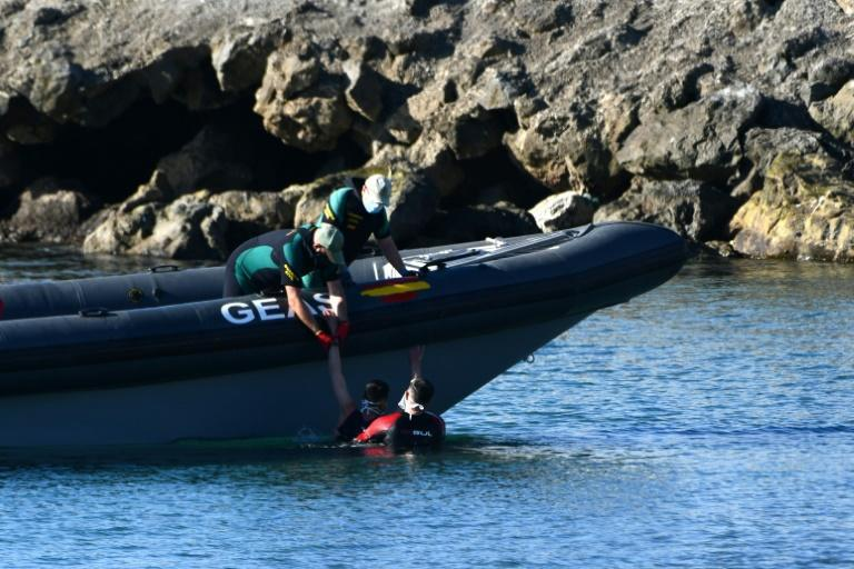 Spanish Civil guards pull a migrant into an inflatable boat after he arrived swimming to the Spanish enclave of Ceuta from neighbouring Morocco on May 17, 2021