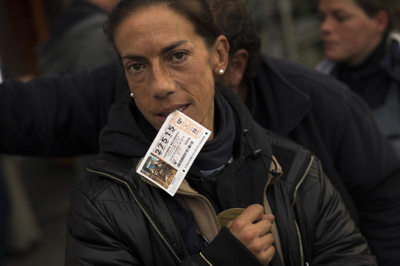 "A woman reacts to the camera while she bites a ticket of the famed Christmas lottery, in Madrid, Friday, Dec. 21, 2012.  Known as ""El Gordo"" (The Fat One) and billed as the world's richest lottery, the drawing will hand out about 2.5 billion of euros (US dlrs 3.3 billion) on upcoming Saturday. The top prize is about 400,000 euros ($530,000) but there are expected to be hundreds or thousands of tickets awarded for that amount. (AP Photo/Daniel Ochoa de Olza)"
