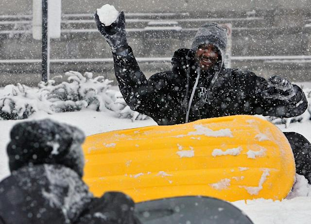 Korey Estes launches a snowball at his son, James Gordon, at the top of Art Hill in front of the St. Louis Art Museum on Sunday, March 24, 2013, in St. Louis. A storm dumped 7 to 9 inches of snow from eastern Kansas into central Missouri before tapering off this morning. (AP Photo/St. Louis Post-Dispatch, J.B. Forbes)