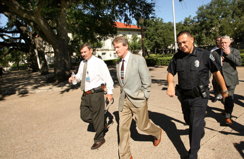 University of Texas President William Powers, Jr., center, walks across the campus mall in Austin with Austin Police Chief Art Acevedo, right, and an unidentified law enforcement officer at left, Tuesday Sept. 28, 2010 after a shooting. A gunman opened fire Tuesday inside a University of Texas campus library then fatally shot himself, and police are searching for a possible second suspect, university police said. (AP Photo/Austin American-Statesman, Jay Janner) MAGS OUT, NO SALES, TV OUT, MANDATORY CREDIT