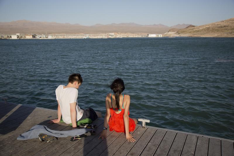 Samuel Nguyen, left, and Mila Phaman, of Montreal, Canada, dip their feet in the water at Echo Bay Marina Monday, June 10, 2013, at Lake Mead National Recreation Area near Overton, Nev. Authorities are warning people to avoid the Overton Arm section of Lake Mead after park officials found dead carp and a mysterious foam there. The foam appeared to be coming from the mouth of the Virgin River and stretched about eight miles down to Echo Bay. (AP Photo/Julie Jacobson)