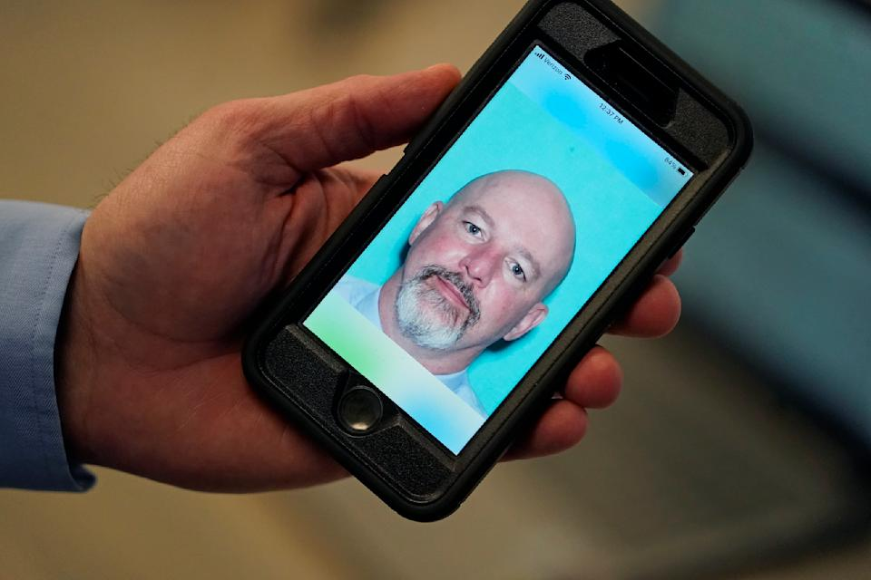 Ryan Williams, with the Utah Drivers License Division, holds his cell phone with the pilot version of the state's mobile ID on Wednesday, May 5, 2021, in West Valley City, Utah. The card that millions of people use to prove their identity to everyone from police officers to liquor store owners may soon be a thing of the past as a growing number of states develop digital driver's licenses. In Utah, over 100 people have a pilot version of the state's mobile ID, and that number is expected to grow to 10,000 by year's end. Widespread production is expected to begin at the start of 2022. (AP Photo/Rick Bowmer)