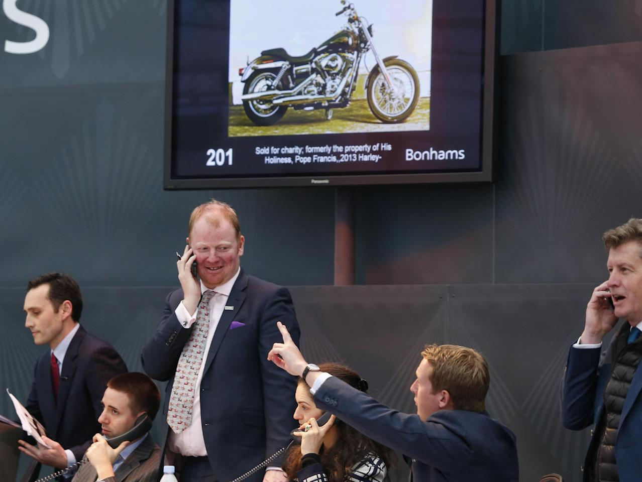 Auction officers on the phone during the auction of the 2013 Harley Davidson Super Glide Custom A 1,585cc which was donated to Pope Francis last year, in Paris, Thursday Feb. 6, 2014. Pope Francis' Harley-Davidson is hitting the road after an unspecified European buyer agreed to pay 241,500 euros ($327,000) including taxes and fees for the motorcycle at a Paris auction to benefit charity. The Bonhams auction house said the telephone buyer agreed to pay far more than the expected pre-sale price of more than 12,000 euros ($16,000) at the auction at Paris' Grand Palais. (AP Photo/Jacques Brinon)